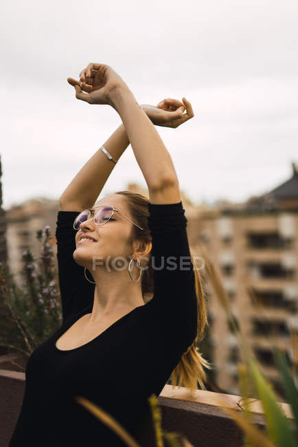 Portrait of young brunette in glasses posing with raised arms at terrace — Stock Photo