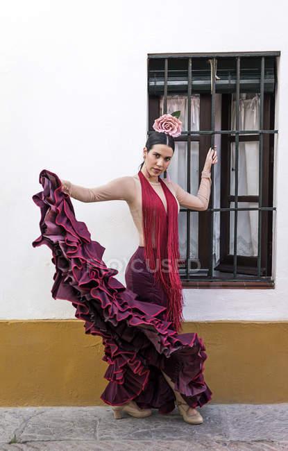 Bailarina flamenca vestida con traje típico sosteniendo falda en la mano y mirando a la cámara - foto de stock