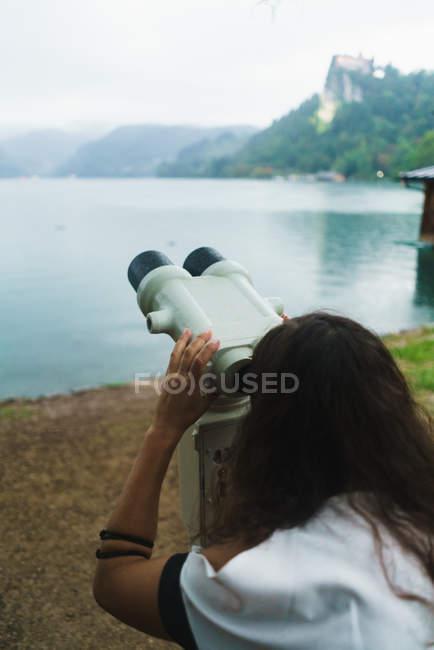 Rückansicht einer brünetten Frau beim Anblick eines Fernglases am Seeufer — Stockfoto