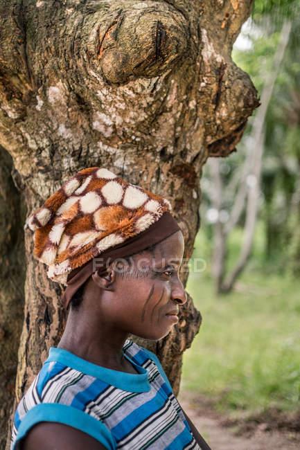BENIN, ÁFRICA - 31 de agosto de 2017: Vista lateral de una mujer africana con cicatrices en la cara posando cerca de un árbol - foto de stock
