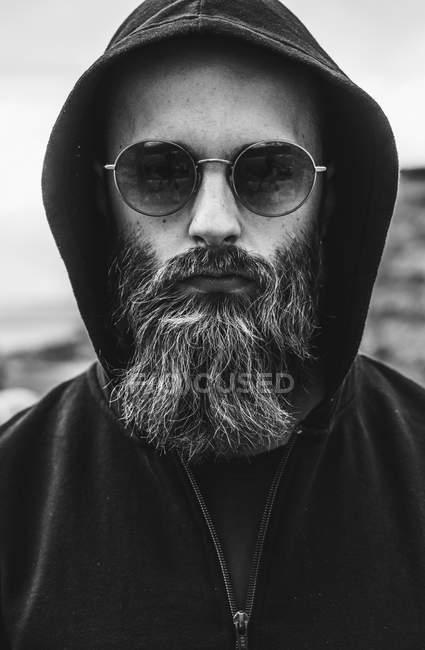 Portrait of bearded man wearing sunglasses and hood — Stock Photo