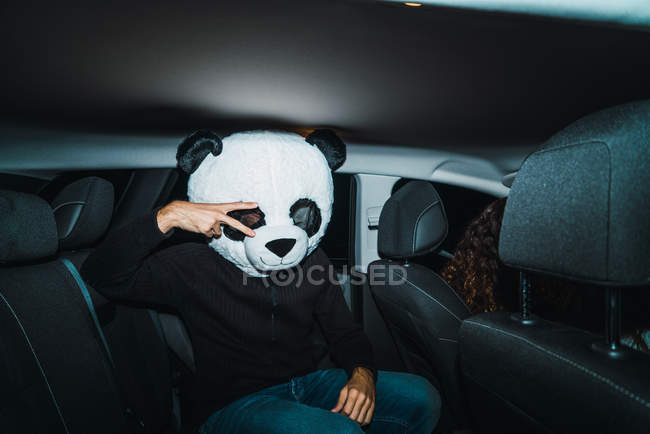 Man wearing panda head mask sitting on back seat of car and showing peace gesture. — Stock Photo