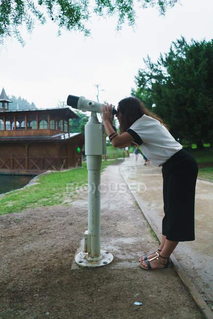 Вид сбоку брюнетка женщина смотрит в бинокль машина экскурсии в парке. — стоковое фото