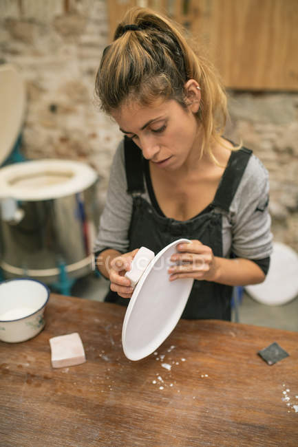 Portrait of concentrated potter creating plates from white clay. — Stock Photo