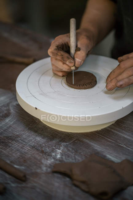 Crop female potter hands carving clay piece — Stock Photo