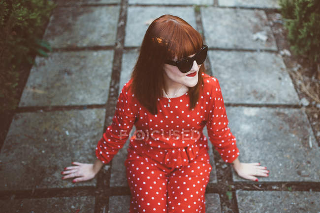 Low angle view of redhead woman in bright red outfit and sunglasses posing happily on ground. — Stock Photo