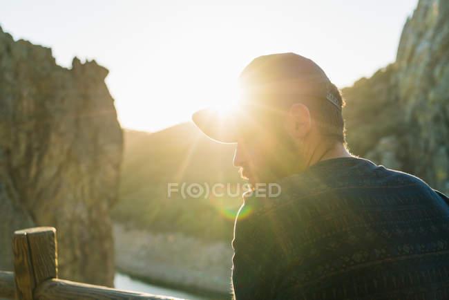 Ritratto dell'uomo che indossa la protezione che osserva sopra la spalla alla soleggiata terrazza rocciosa — Foto stock