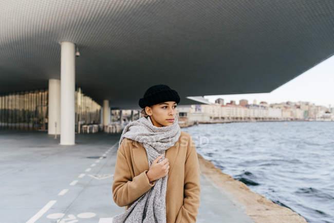 Portrait de jeune femme posant dans la rue et regardant ailleurs — Photo de stock