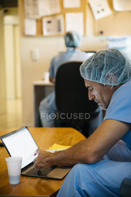 Side view of doctor sitting at laptop and talking on phone — Stock Photo