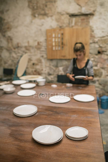 Shiny handcrafted plates on table over female potter working with clay at workshop — Stock Photo