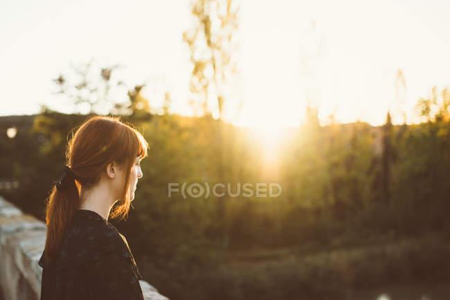 Side view of ginger girl posing on rural bridge in sunlight — Stock Photo
