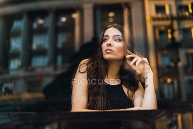 Blick durchs Fenster auf Brünette Mädchen posiert am Café-Tisch und wegsehen — Stockfoto