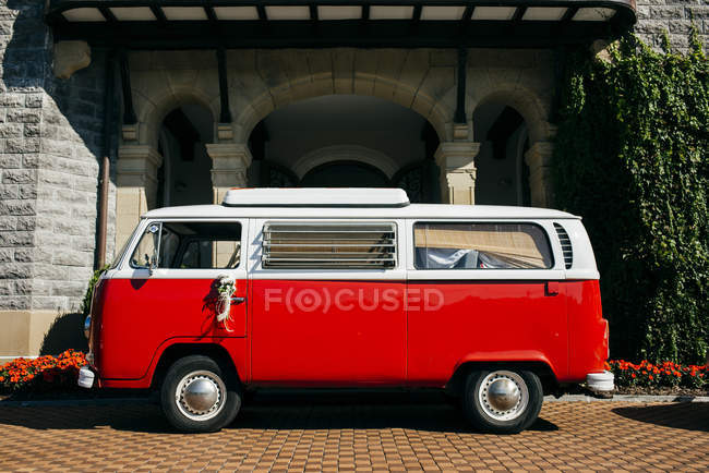 Red van for parked on paved street in sunlight. — Stock Photo
