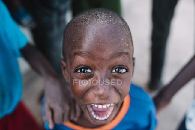Goree, Senegal- 6 de diciembre de 2017: Retrato de bajo ángulo del expresivo niño africano gritando felizmente y mirando a la cámara . - foto de stock
