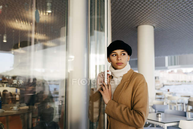 Portrait of woman leaning on cafe entrance and looking away — Stock Photo