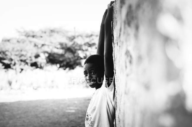 Гори, Сенегал - 6 декабря 2017 года: Боковой вид веселого африканского мальчика висит на стене и смотрит в камеру — стоковое фото
