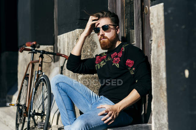 Portrait of man sitting by bicycle on street — Stock Photo
