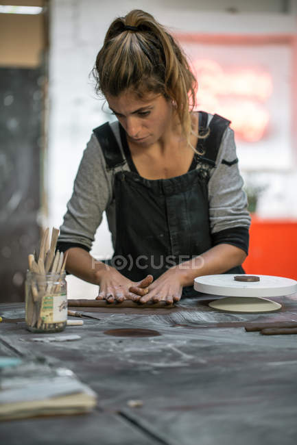 Portrait of female potter forming clay stick on wooden table at workshop — Stock Photo