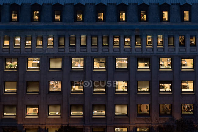Full frame shot of office building facade at night — Stock Photo
