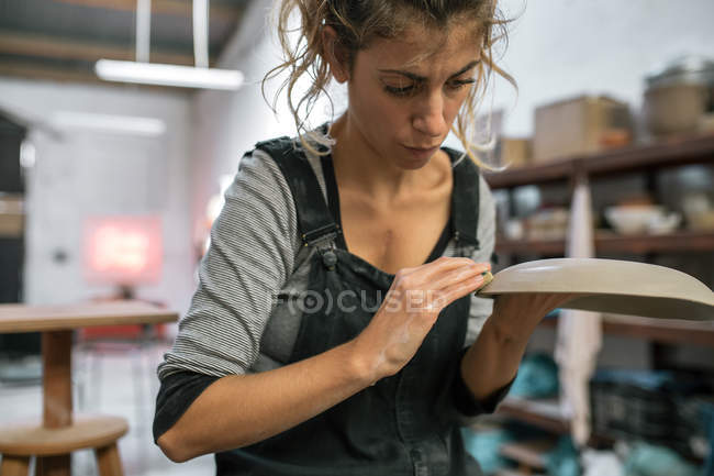 Portrait of potter moistening clay plate in workshop — Stock Photo
