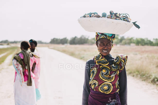 Goree, Sénégal- 6 décembre 2017 : Portrait d'une Africaine souriante portant un panier sur la tête et marchant sur la route . — Photo de stock
