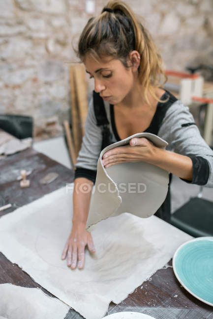 Portrait of female potter preparing workplace at pottery workshop — Stock Photo