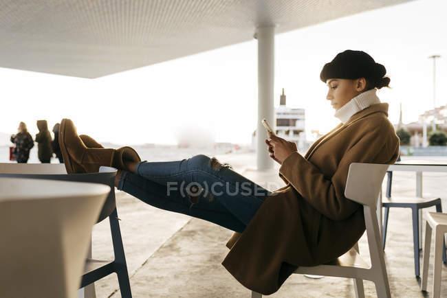 Vista laterale della donna in cappotto caldo con i piedi sul tavolo navigazione smartphone — Foto stock