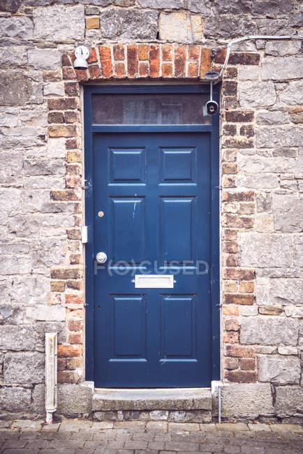 Esterno della facciata con il portello blu in muro di mattoni — Foto stock