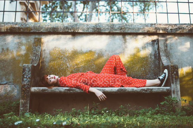 Вид збоку молодих redhead пристрасний жінка в червоних лежачи на шорсткою кам'яна лава — стокове фото
