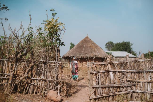 Rückansicht eines Mannes, der zu reetgedeckten Bungalows in einem afrikanischen Dorf geht. — Stockfoto