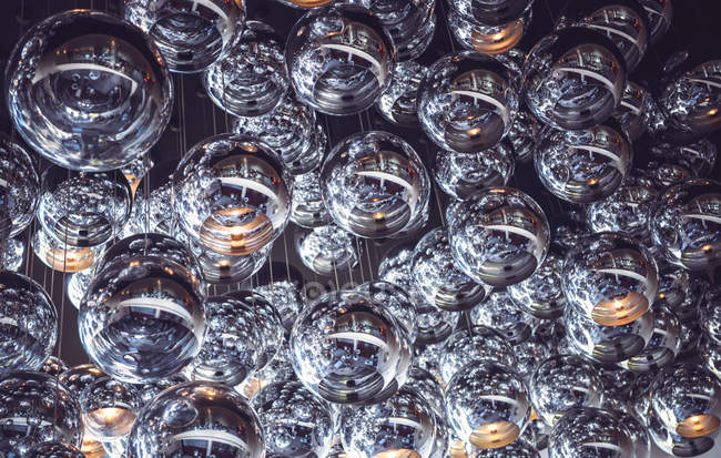 Low angle view of glass sphere lamps hanging on ceiling . — Stock Photo