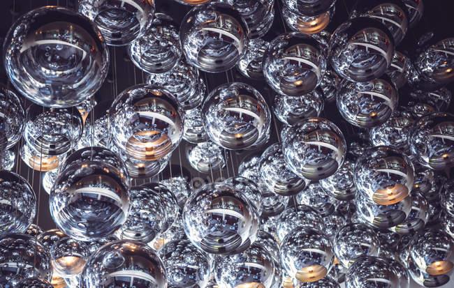 Vista de ángulo bajo de las lámparas de cristal esfera colgando en el techo - foto de stock