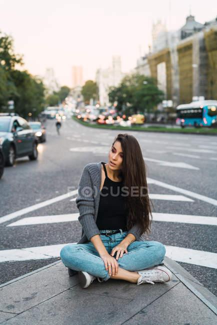 Брюнетка дівчина в повсякденний одяг, сидячи на сторону ходити на вулиці сцени — стокове фото