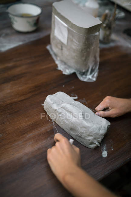 Crop potter hands cutting piece of clay with string — Stock Photo