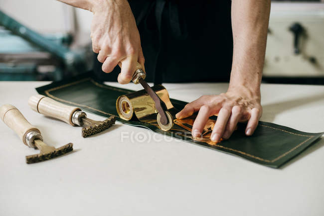 Crop shot of workman using tools and gold material while imprinting on leather. — Stock Photo