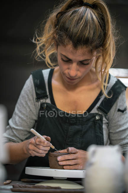 Portrait of concentrated female potter working with clay — Stock Photo