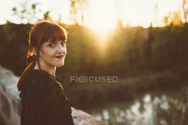 Portrait of redhead woman smiling at camera at countryside bridge. — Stock Photo