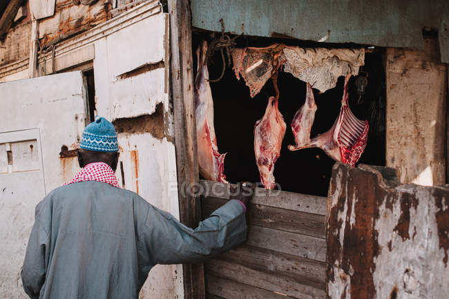 Rear view of man standing on entrance of stable with hanging meat — Stock Photo