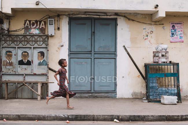 Goree, Sénégal- 6 décembre 2017 : Vue de côté d'une Africaine courant le long de la rue d'une petite ville africaine . — Photo de stock