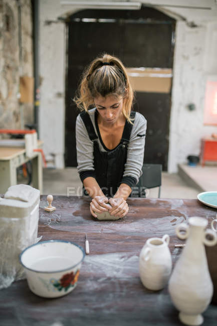 Front view of concentrated potter kneading clay on table at workshop — Stock Photo