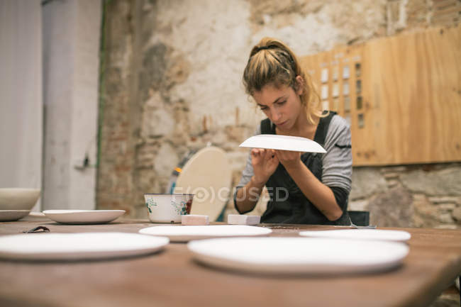 Concentrated woman in apron sitting at table and creating plates from white clay. — Stock Photo