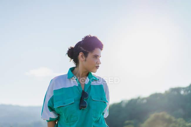 Чувственная брюнетка женщина с булочкой в голове позирует на lokeposing в солнечном свете — стоковое фото