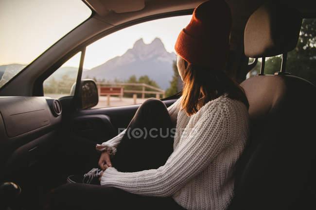 Женщина в красной шляпе, сидя в машине и, глядя из окна во время поездки в сельской местности, вид сбоку — стоковое фото