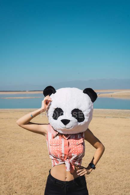 Ragazza in posa nella testa del giocattolo di panda su sfondo di spiaggia di sabbia di lago — Foto stock