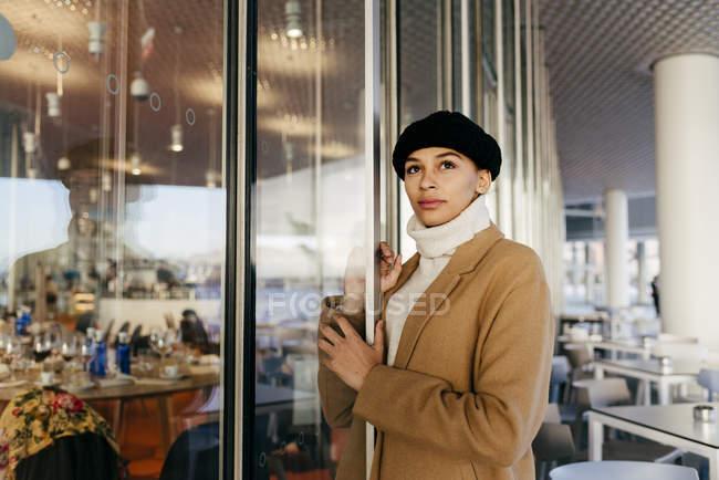 Portrait de femme penché sur l'entrée du café et regardant loin rêveur — Photo de stock