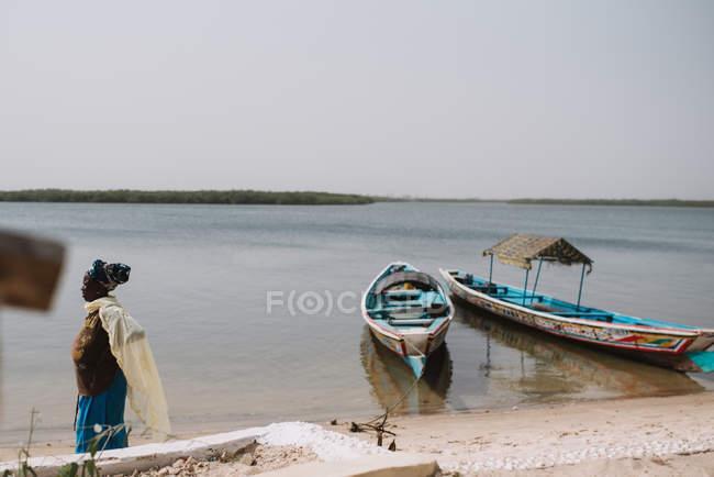 Yoff, Сенегалу - 6 грудня 2017: вид збоку Жінка вигулює на березі річки з пошарпаний Вітрильники при сонячному світлі. — стокове фото