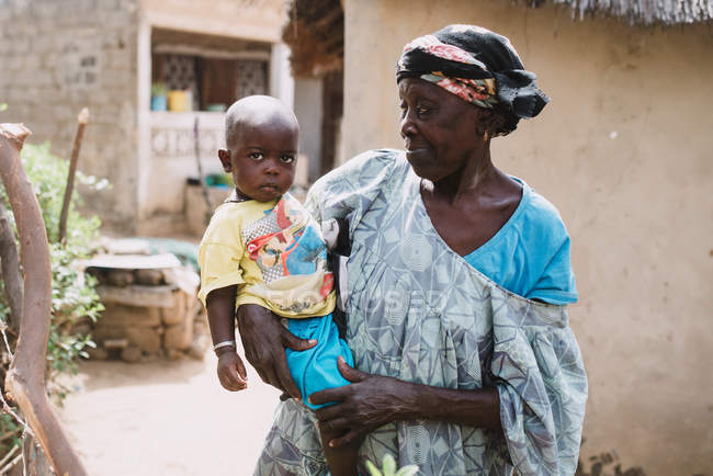Yoff, Senegal- December 6, 2017: Elderly  woman holding little boy on hands on background of rural village. — Stock Photo
