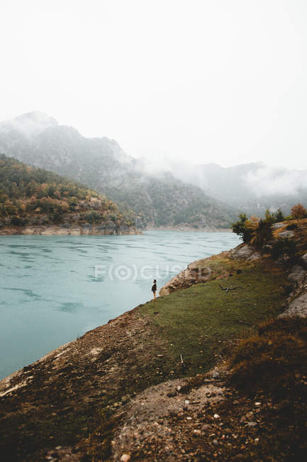 Отдаленный взгляд на человека, стоящего на берегу реки против облачных холмов — стоковое фото
