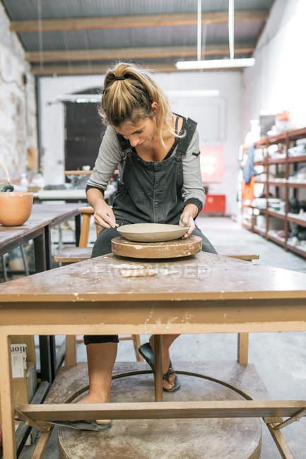 Frontansicht Töpferinnen gestalten Tonteller mit Instrument in der Werkstatt — Stockfoto