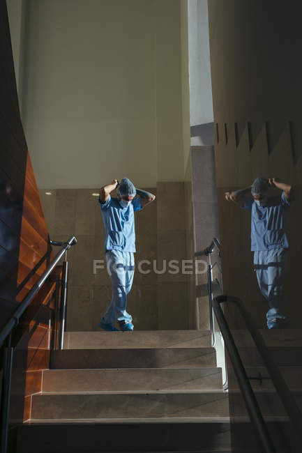 Surgeon in uniform adjusting mask and walking down stairs — Stock Photo